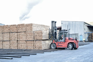 Gaffeltruck kjører stabler med planker