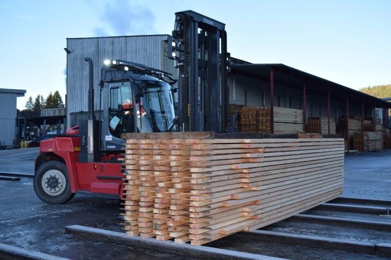 Gaffeltruck kjører stabel med planker